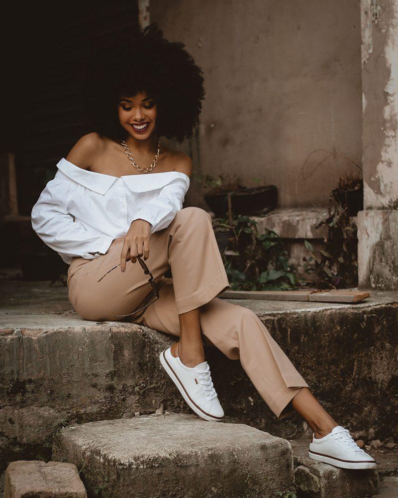 photo-of-smiling-woman-sitting-on-concrete-block-posing-2873674